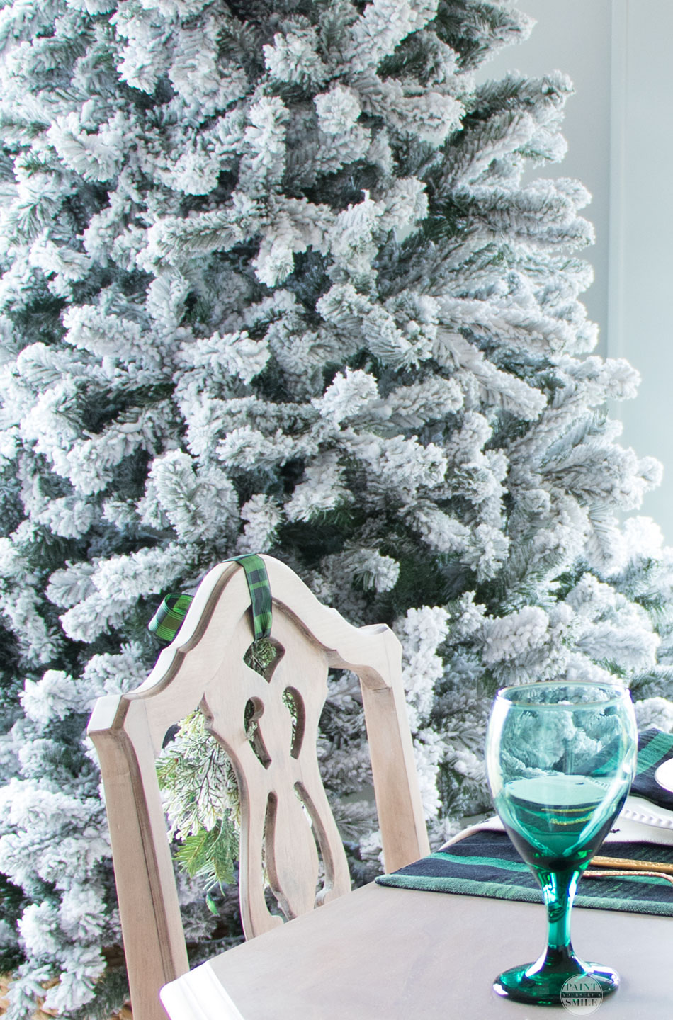 Stunning winter wonderland dining room with DIY flocked window wreaths, DIY flocked mini trees, and gorgeous table scape. Snowy neutral winter décor ideas